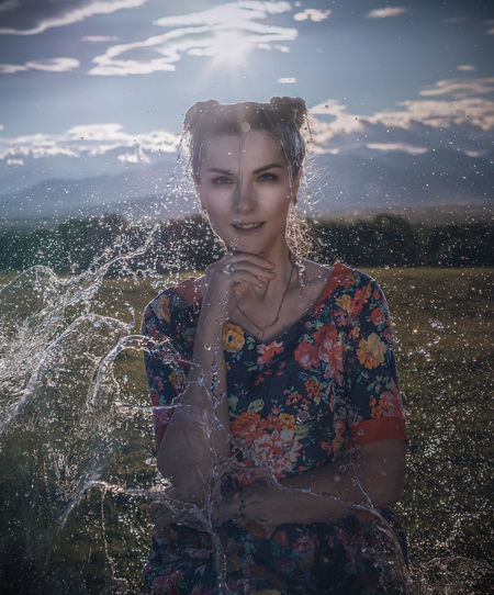 Portrait of beautiful woman standing against water
