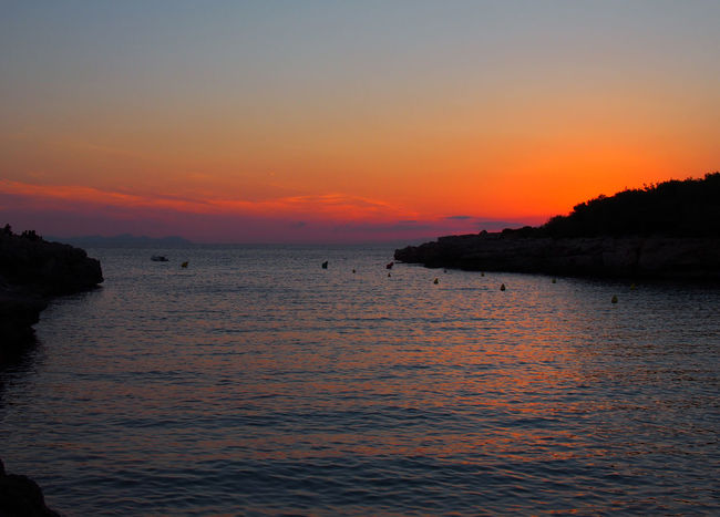 glowing glowing evening twilight after sunset in the cala santandria bay in ciutadela menorca with a beautiful orange sky reflected in a dark sea with the land in silhouette Bay Of Water Dusk Sunset Sky Water Scenics - Nature Sea Beauty In Nature Tranquil Scene Tranquility Idyllic Waterfront Land Horizon Horizon Over Water Beach Nature Orange Color Non-urban Scene Cloud - Sky No People Outdoors