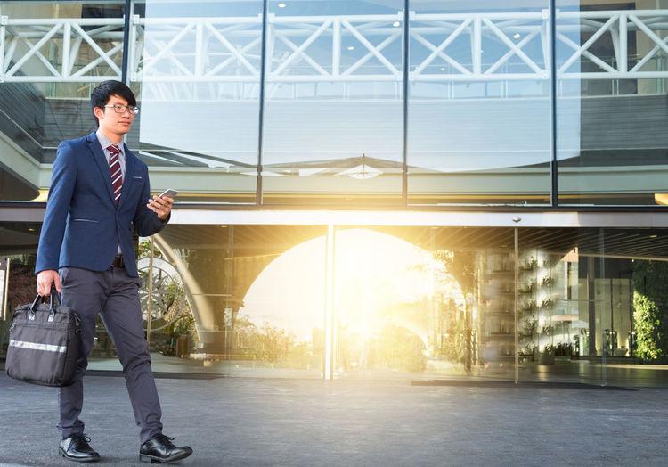 Full length of businessman walking outside office building
