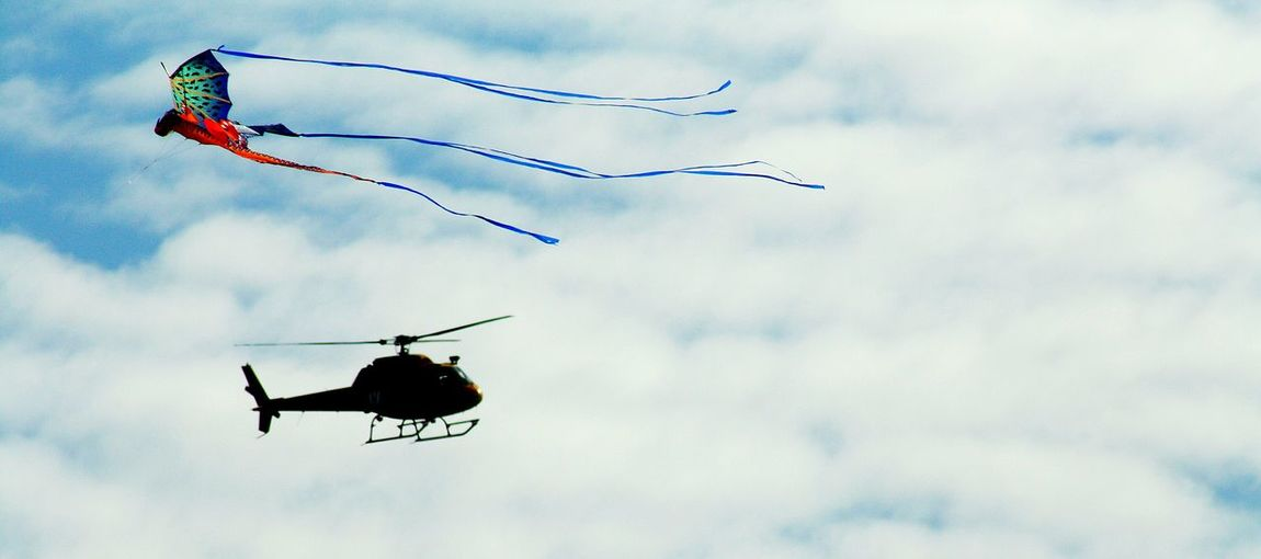 Low Angle View Of Helicopter And Kite Flying Against Cloudy Sky