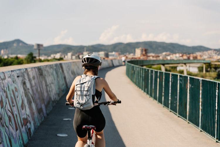 Rear view of man riding motorcycle on footbridge