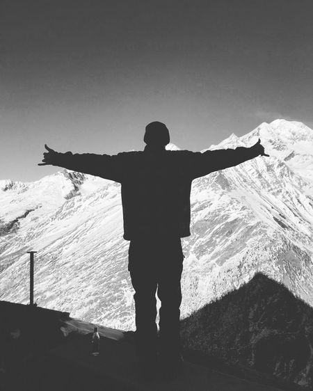 Silhouette man with arms outstretched standing against snow capped mountains