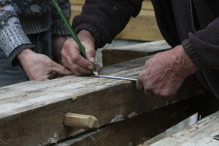 Midsection of carpenters measuring wood while working in carpentry workshop
