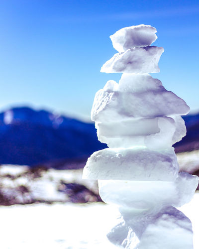 Close-up of snow covered stack against blue sky