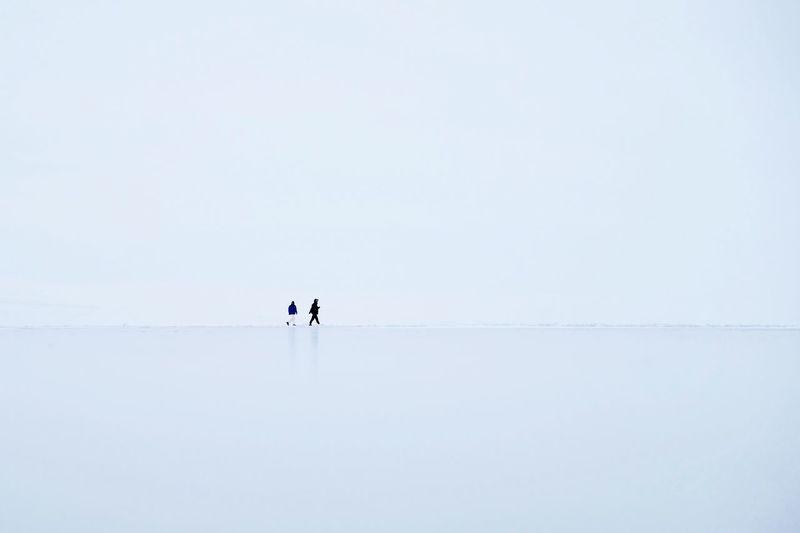 Men walking on frozen lake against clear sky