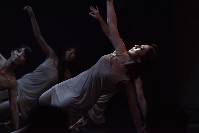 Women dancing against black background