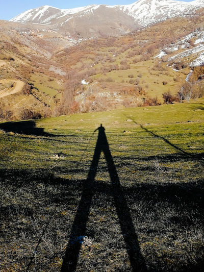 Shadow of person on field against mountain