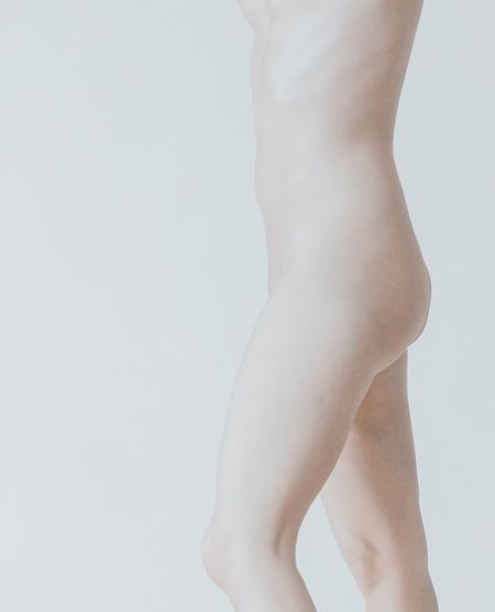 Low section of woman standing against white background