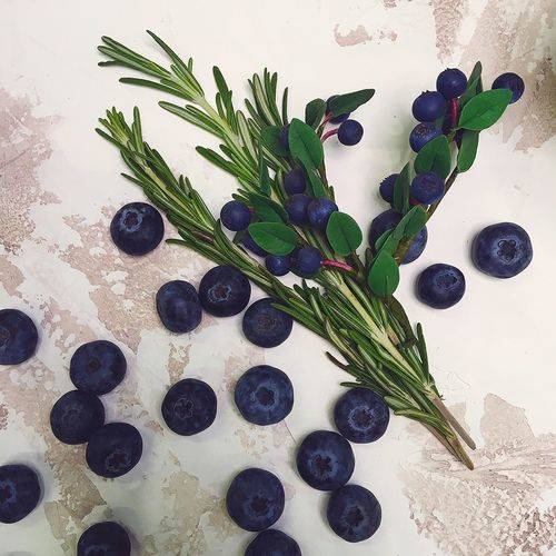 High angle view of blueberries with rosemary on table
