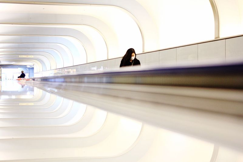 Woman Wearing Mask In White Moving Walkway