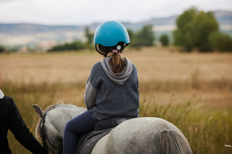 5-year-old girl riding on a horse, in a hipico club. infalltil sport concept.