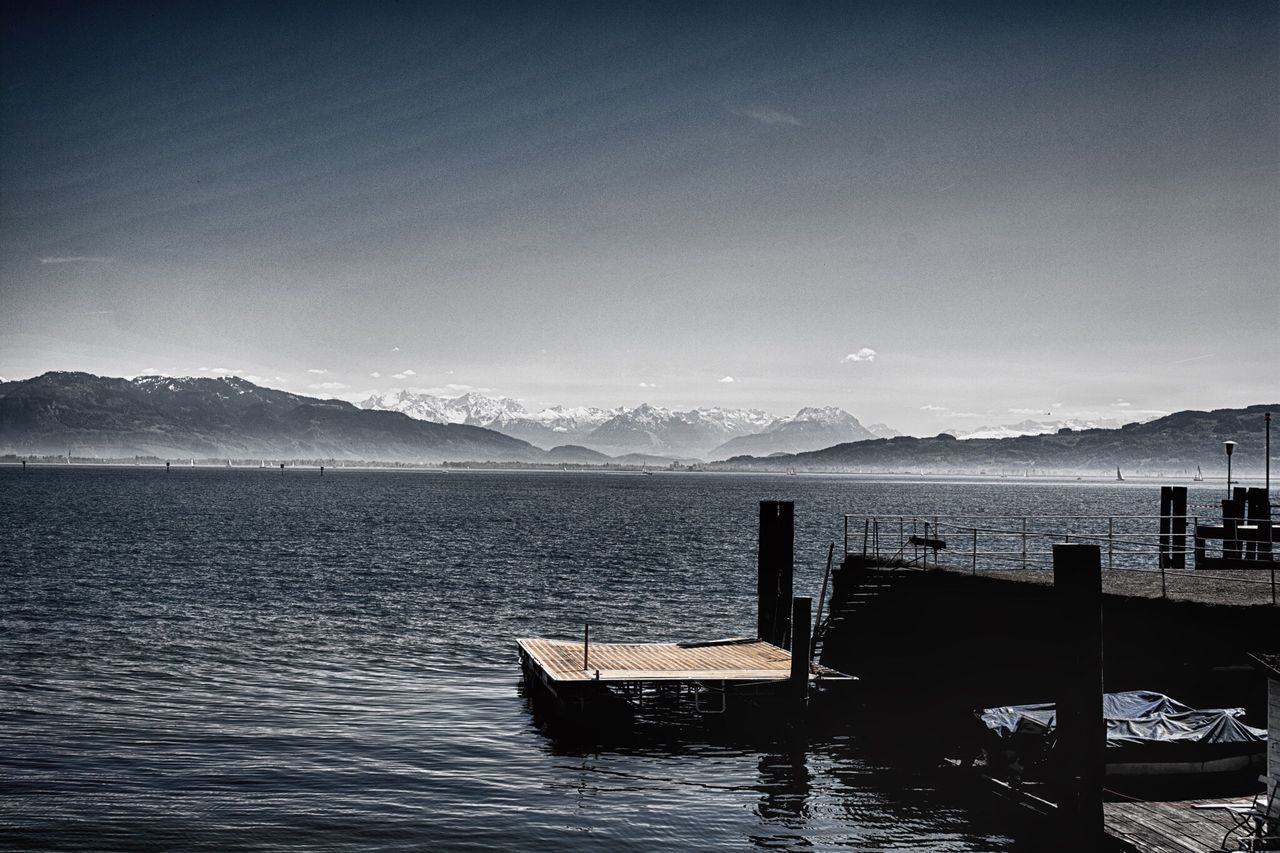 mountain, water, scenics, tranquility, nature, beauty in nature, tranquil scene, mountain range, no people, nautical vessel, sky, sea, wood - material, transportation, outdoors, day, clear sky