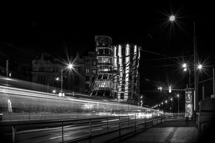 Light trails on bridge over street at night