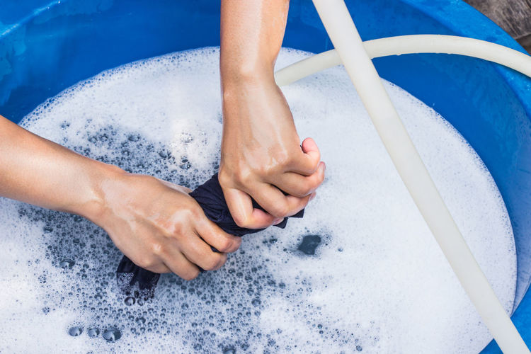Female hands wash clothing by hand with detergent in focus and space for text. Blue Basin Casual Housework Washing Woman Black Bubble Cleaners Clothes Foam Hand Hose Human Body Part Human Hand Lifestyles Nature Outdoors People Shirt Utensil Wash Water Wet White