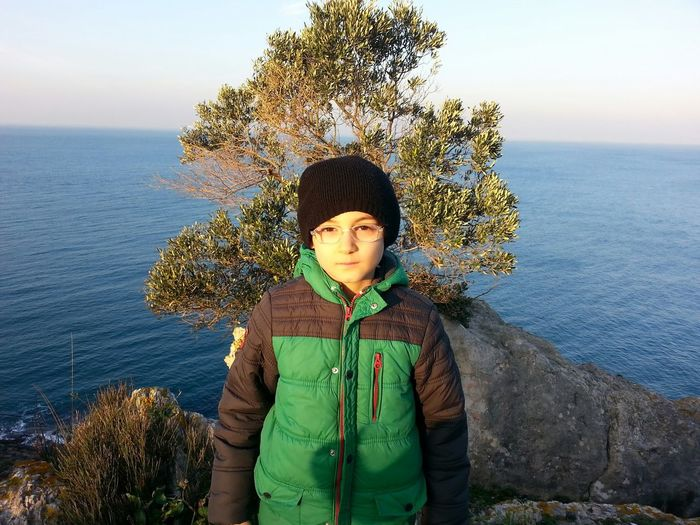 Portrait of boy standing against sea and sky