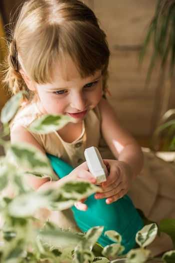 High angle view of girl spraying water on plants at home
