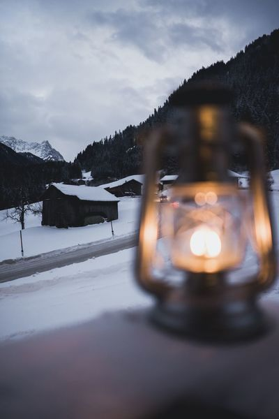 Oil lantern in front of mountain panorama Real People Real Life Live Authentic Travel Adventure Outdoors Lamp Oil Lamp Oil Lantern Snow Winter Cold Temperature Sky No People Nature Weather Mountain Illuminated Outdoors Cloud - Sky Tranquility Scenics Landscape Day Tree Close-up Beauty In Nature