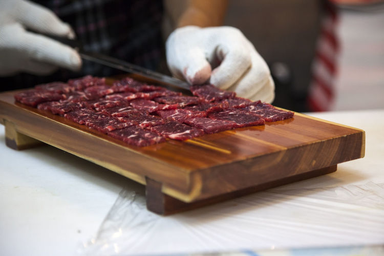 Midsection Of Man Cutting Meat On Chopping Board In Kitchen