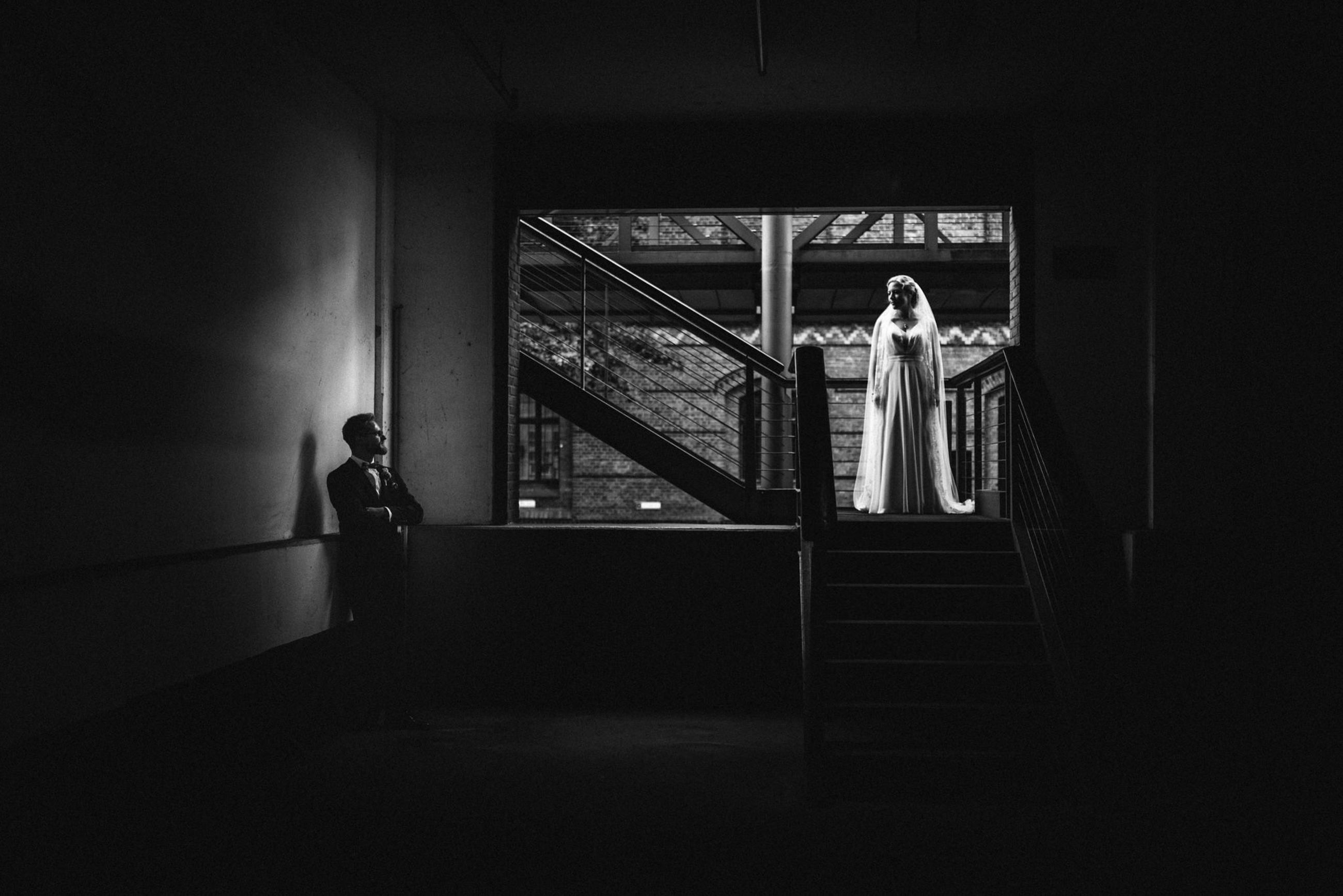 indoors, architecture, railing, men, real people, built structure, staircase, standing, full length, women, rear view, people, adult, two people, building, day, lifestyles, wedding dress, steps and staircases, couple - relationship