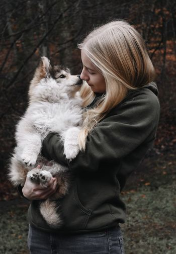 Blonde woman holding a puppy dog, kissing