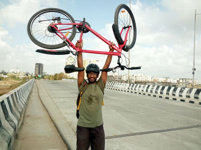 Happy cyclist carrying bicycle while standing on highway in city against sky