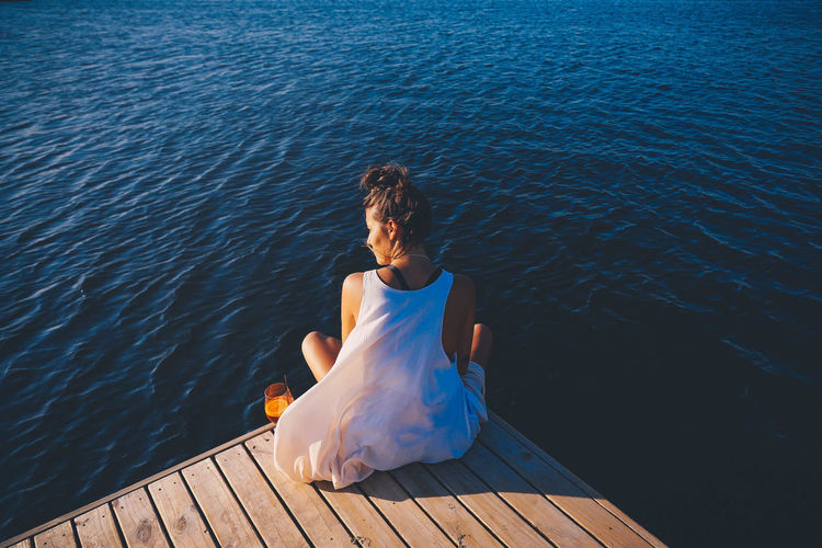 Adult Bride Day Full Length Jetty Lake Leisure Activity Lifestyles Nature One Person Outdoors People Pier Real People Rear View Sitting Water Wedding Dress Women Young Adult Young Women
