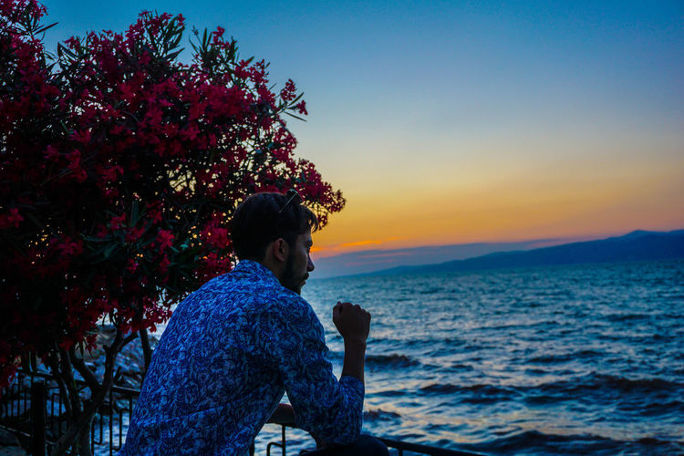 Man looking at sea during sunset