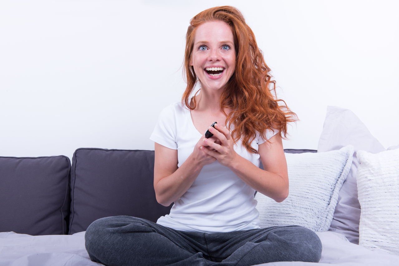 Portrait Of Cheerful Woman Sitting On Sofa Against White Background