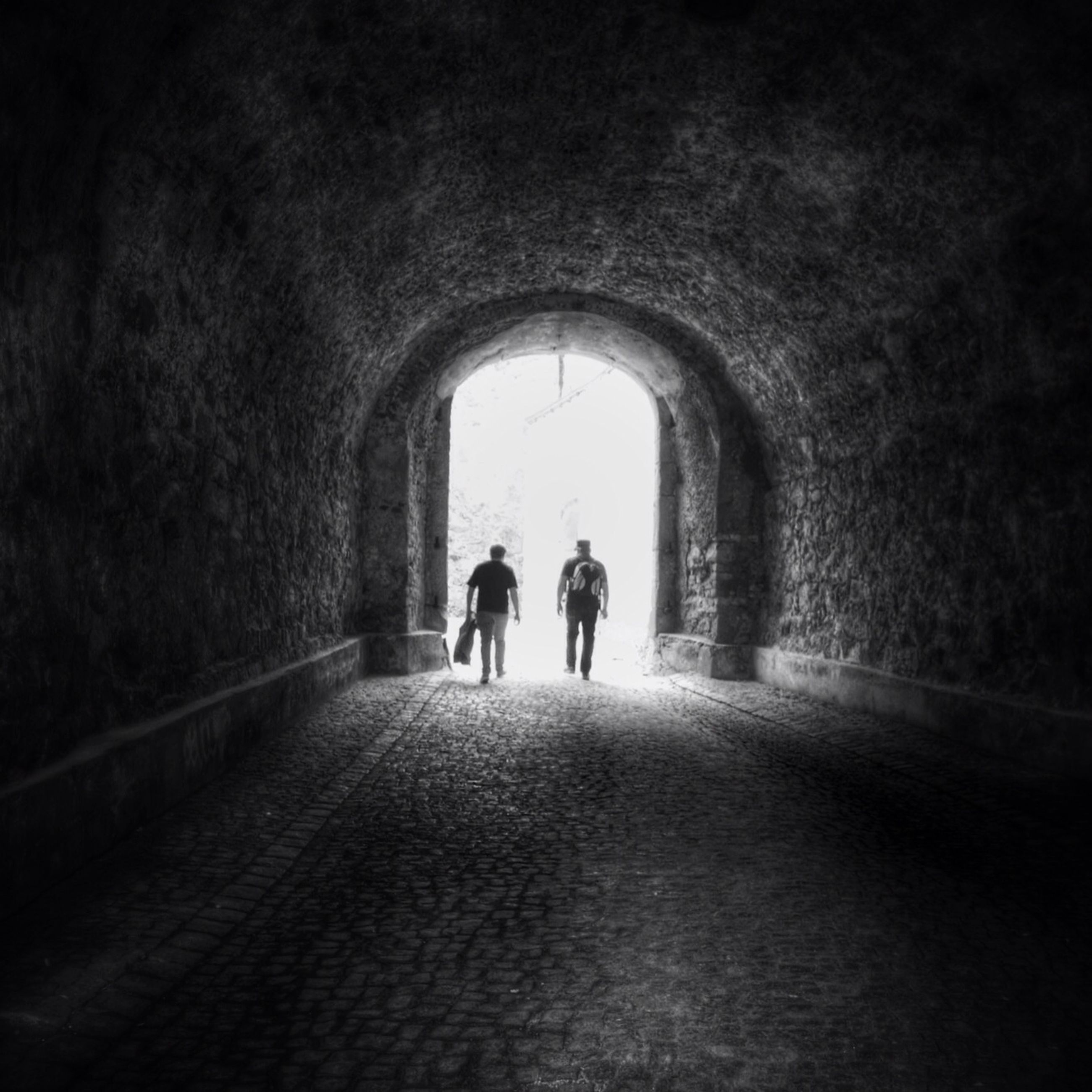 tunnel, indoors, arch, full length, walking, rear view, men, lifestyles, silhouette, archway, the way forward, leisure activity, togetherness, person, architecture, light at the end of the tunnel, built structure
