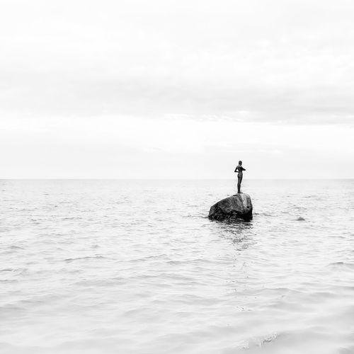 Man in sea against sky