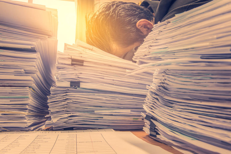 Tired businessman on stacked papers at desk in office