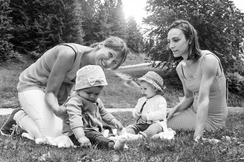 Smiling mothers with daughters relaxing at park