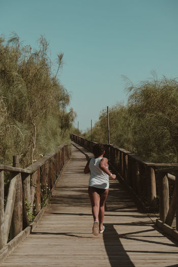 Rear view of girl running on boardwalk against clear sky