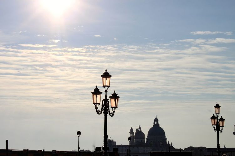 Street lights and silhouette church against sky during sunset