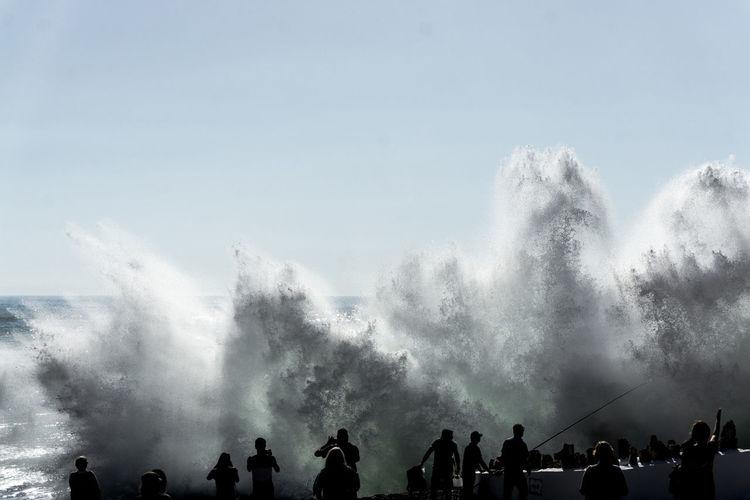 People looking at waterfall against sky