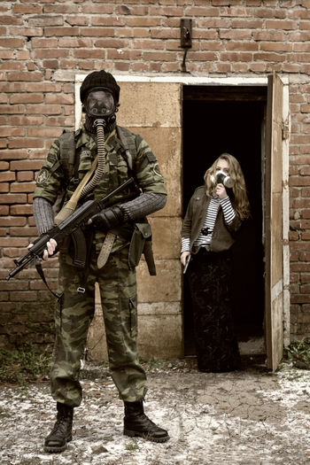 Army soldier holding rifle with civilian standing by door