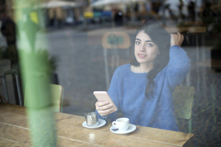 Young beautiful woman drinking coffee and use her smartphone sitting indoor in urban cafe. Cafe city lifestyle. Casual portrait of beautiful girl One Person Cup Young Adult Coffee Cup Mug Smiling Portrait Coffee - Drink Food And Drink Holding Coffee Adult Table Drink Young Women Women Waist Up Lifestyles Real People Casual Clothing Hair Beautiful Woman Wireless Technology Hairstyle Tea Cup