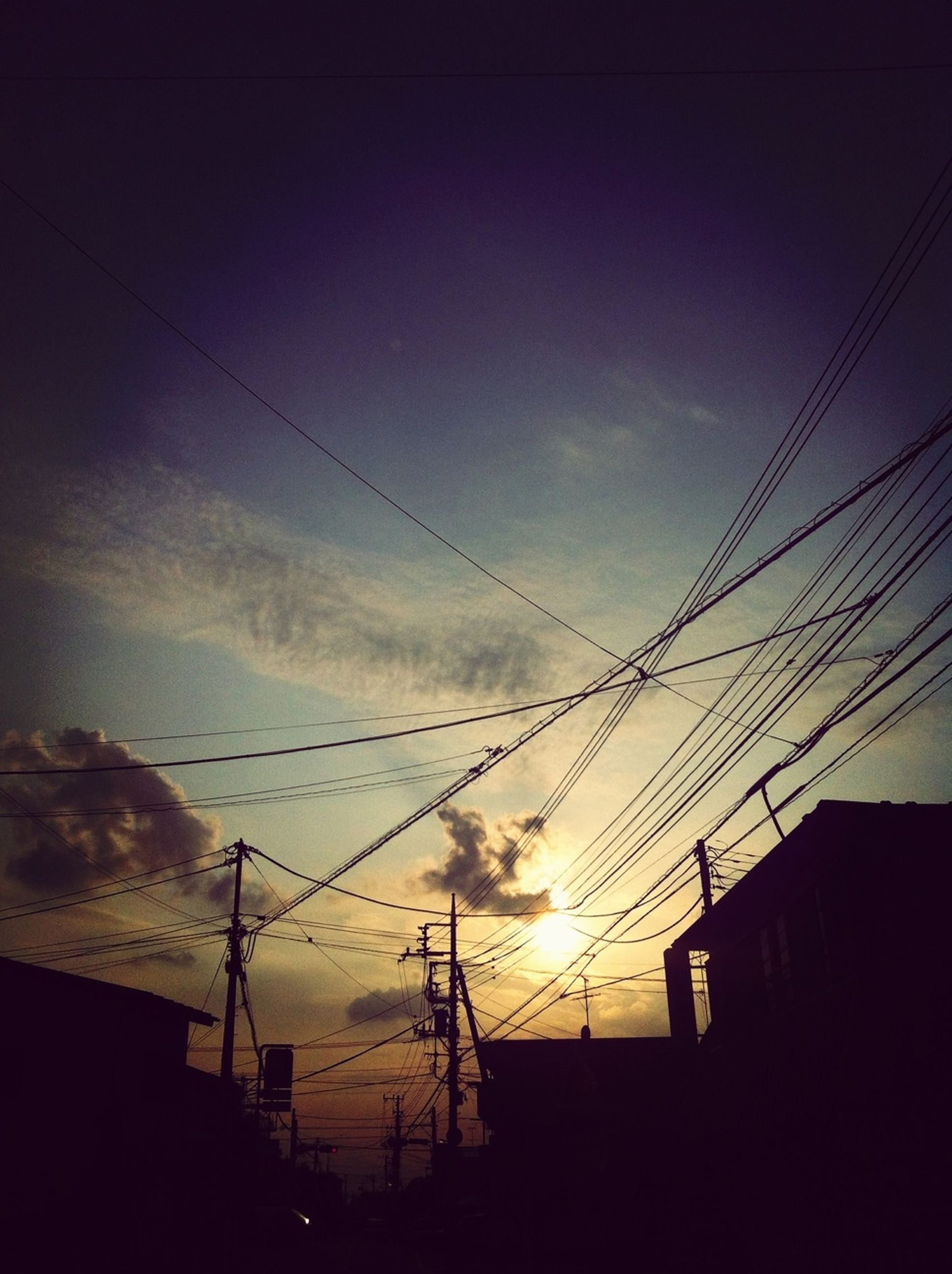 power line, electricity pylon, electricity, power supply, cable, low angle view, sky, connection, silhouette, fuel and power generation, built structure, building exterior, architecture, power cable, technology, sunset, cloud - sky, house, dusk, cloud