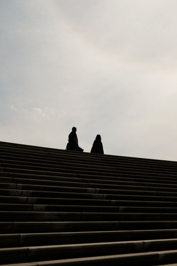 Low angle view of silhouette people on staircase against sky