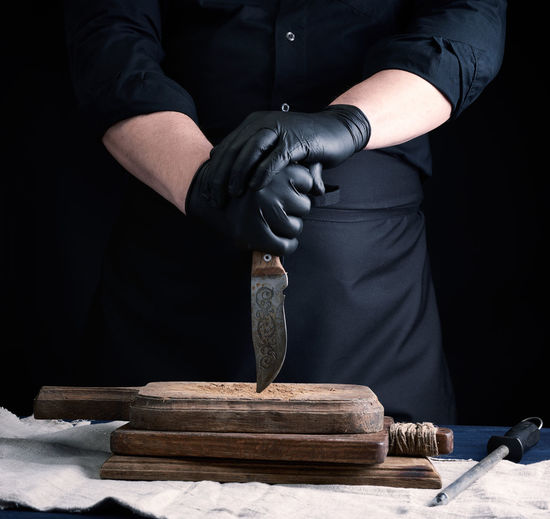 Midsection of man working on wood against black background