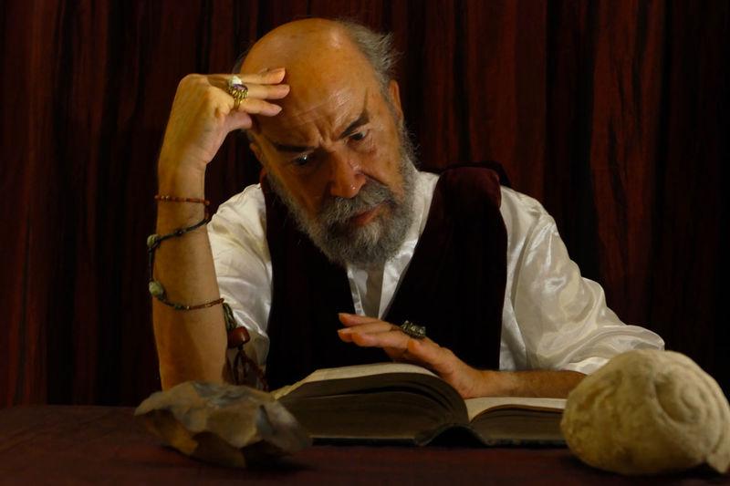 Portrait of man sitting on book