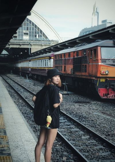 Woman with backpack standing on railroad station platform