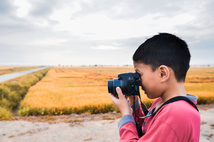 Boy photographing with camera on field against sky