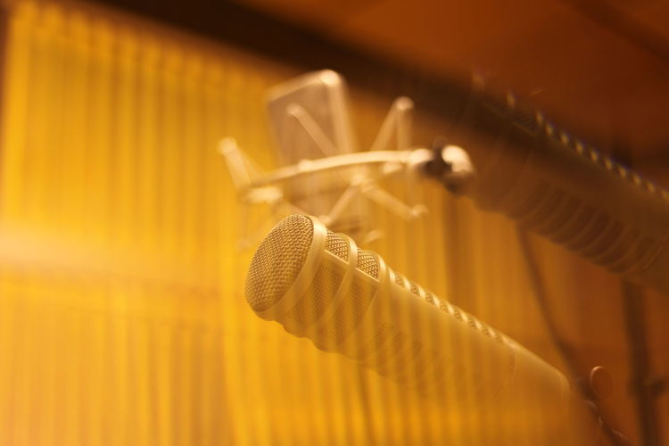 Close-up of microphones in recording studio seen through glass