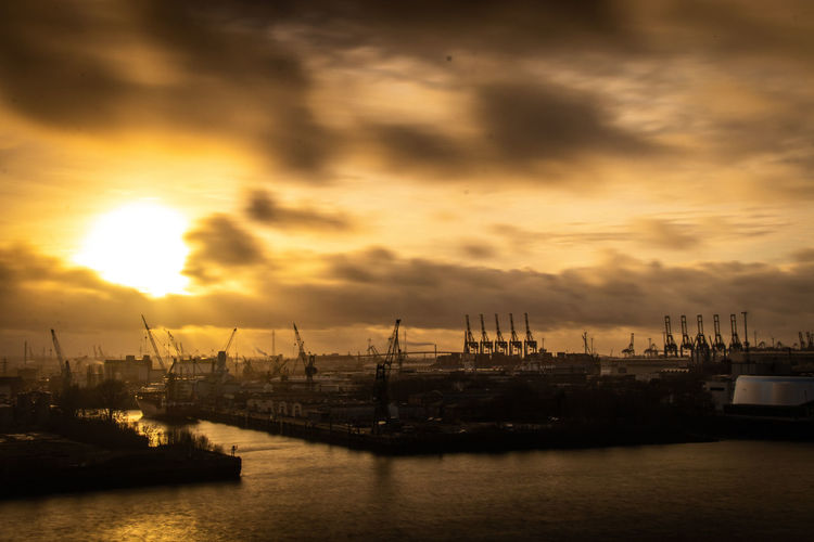 Sailboats at harbor against sky during sunset