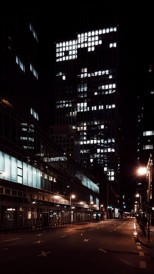 Low angle view of illuminated buildings in city street at night