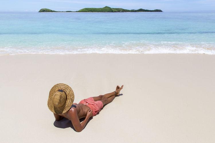 Man lying on sand at beach