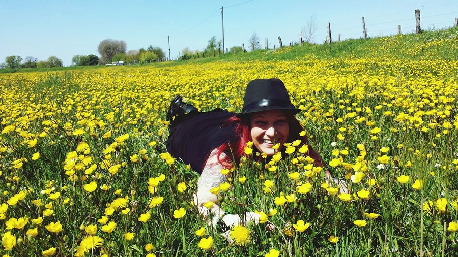 Smiling woman lying in field of yellow flowers