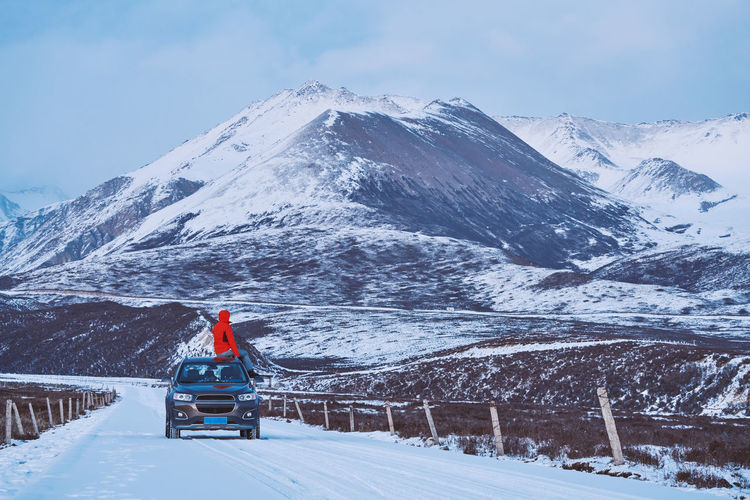 Man sitting on car roof against snowcapped mountains