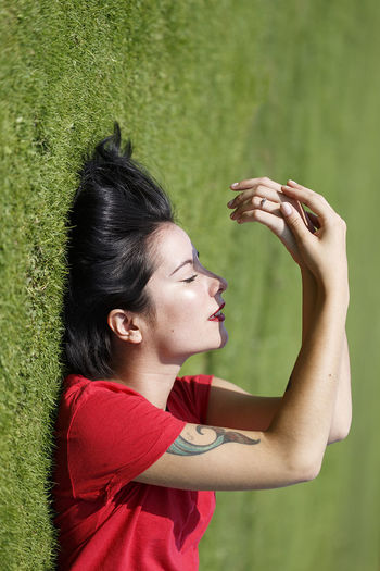 Side view of young woman standing in grass